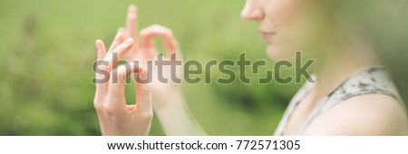 Close-up of hand of woman practicing yoga in the garden