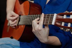 Close up of hand of young woman in the blue shirt and jeans playing acoustic guitar. Girl picks a barre chord clamping frets on the fretboard