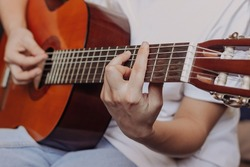 Close up of hand of young woman in the white t-shirt and blue jeans playing acoustic guitar. Girl picks a barre chord clamping frets on the fretboard