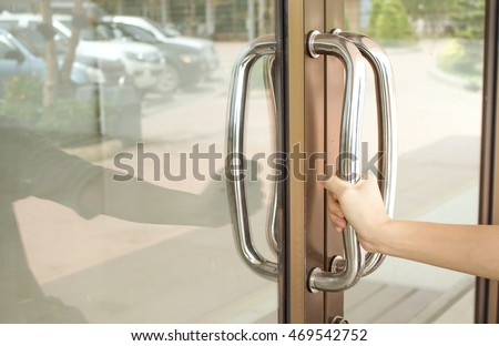Close-up of hand open Aluminum glass door or Hand holding handle.