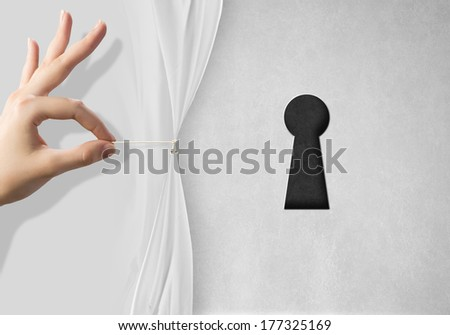Close up of hand opening white curtain with keyhole behind it