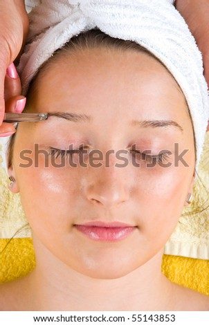 Close up of hand plucking woman eyebrow