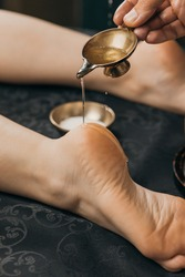 Close-up of hand pouring oil on foot. Oil applicator for relaxing massage. Gold body treatment and diamond powder exfoliating scrub.