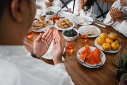 close up of hand praying before eating. muslim open arm and pray