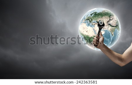 Close up of hand spinning nut on Earth planet. Elements of this image are furnished by NASA