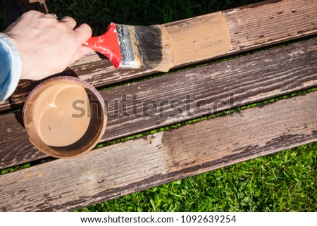 Close up of hand staining wooden furniture with brush and brown protective wood stain, repainting old terrace furniture in spring. Refreshing, giving new look concept. #1092639254
