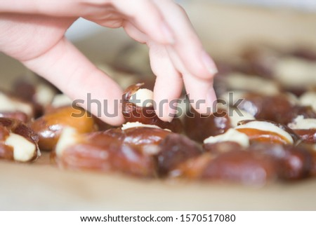 Close up of hand taking a marzipan stuffed date