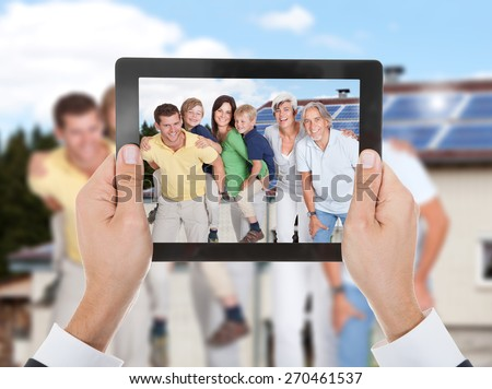 Close-up Of Hand Taking Photo Of Two Generation Family With Digital Tablet