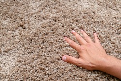 Close up of hand touching soft carpet. Gentle and fluffy carpet between fingers.