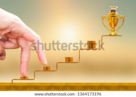 Close up of hand with climb up on a stacking five gold coin with growing on golden steps and trophy with money bag as destinations on sunlight background, Business investment and saving money concept. #1364173196