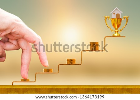 Close up of hand with climb up on a stacking five gold coin with growing on golden steps and trophy with home as destinations on sunlight background, Loan for real estate or buy the house concept. #1364173199