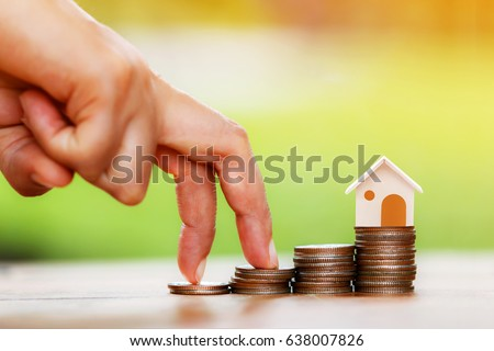 Close up of hand with climb up on a stacking gold coins and home as destinations, Loans for real estate or buy a new house in the future concept.