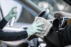 Close up of hand with gloves spraying alcohol,disinfectant spray on steering wheel in her car,contamination of germs or bacteria,wipe clean surfaces that are frequently touched