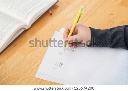 close up of hand with pencil doing math