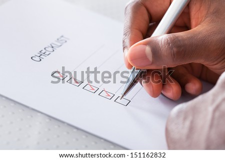 Close-up Of Hand With Red Pen Marking A Check Box