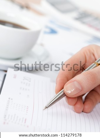 Close up of hand writing in the notebook. Cup of coffee stands nearby