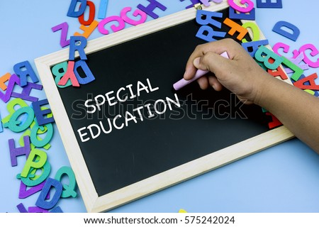 Close up of hand writing SPECIAL EDUCATION on chalk board with piles of alphabet surrounding it. Education concept