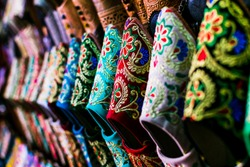 Close-up of handmade colorful embroidered cloth slippers (babouches) for sale in an artisan market in Morocco. Traditional moroccan shoes. Oriental style concept.