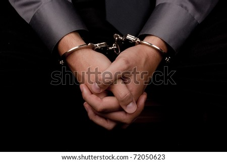 Close-up of hands handcuffed, arrested for questioning.