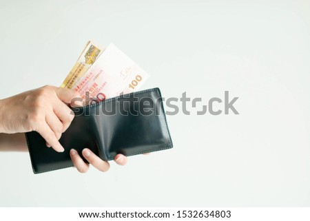 Close-up of hands holding a short wallet and one hand bring out Hong Kong money; in the currency of Dollar Hong Kong or HKD; from the wallet to pay for something on white background with copy space.