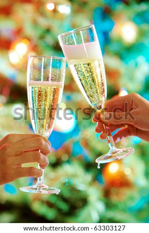 Close-up of hands holding flutes of champagne doing clink - stock photo