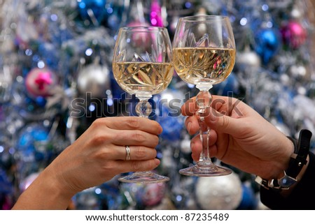Close-up of hands holding glasses of champagne and doing clink against new year tree
