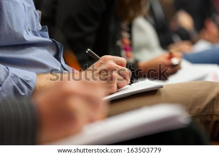 Close-Up Of Hands Holding Pens And Making Notes At The Conference
