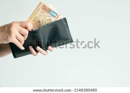 Close-up of hands holding the short wallet and one hand bring out Hong Kong money; in the currency of Dollar Hong Kong or HKD; from the wallet to pay for something on white background with copy space.