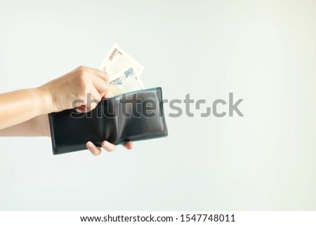 Close-up of hands holding the short wallet and one hand bring out Japan money; in the currency of Yen or JPY; from the wallet to pay for something on white background with copy space.