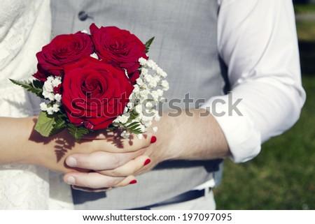 Close-up of hands holding wedding bouquet, Uppsala, Sweden