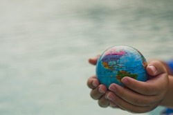 close up of hands holding world sphere over water