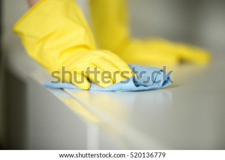 Close up of hands in rubber protective yellow gloves cleaning the white surface with a rag. Home, housekeeping concept
