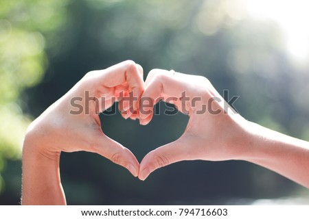 Close-up of Hands in shape of love heart on nature green bokeh  #794716603