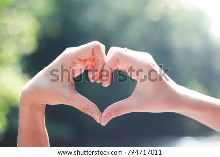 Close-up of Hands in shape of love heart on nature green bokeh  #794717011