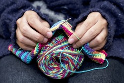 Close-up of hands knitting colorful wool