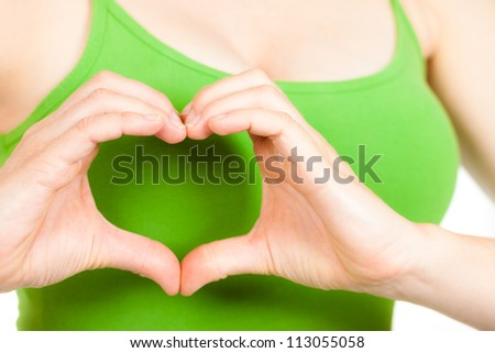 Close-up of hands making a love heart in front of a woman's breast.
