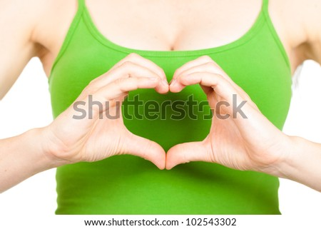 Close-up of hands making a love heart in front of a woman's heart