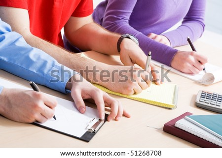 Close-up of hands making written review of planned work - stock photo