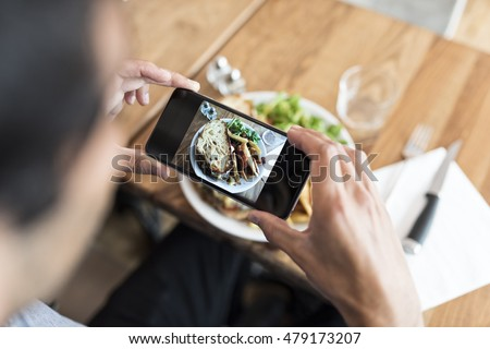 Close-up of hands male in the restaurant taking picture food with his smart phone