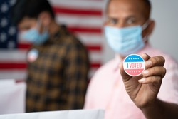 Close up of Hands, Man in medical mask showing I voted Sticker at polling booth with US flag as background - concept in person voting at US election