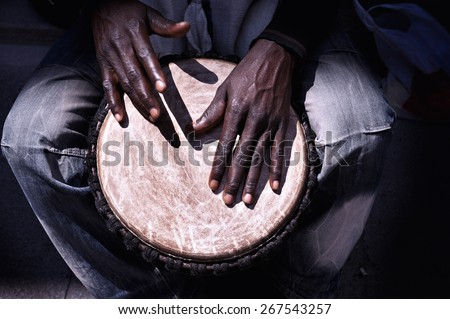 Close up of hands of a black man playing a drum