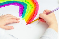 Close up of hands of a child drawing a rainbow on white paper in the quarantine time.