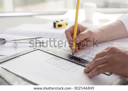 Close up of hands of architect drawing sketches of construction. He is holding a pencil and a ruler