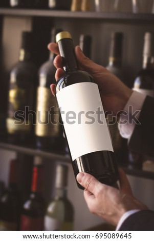 close up of hands of Caucasian men with white shirt holding a red wine bottle with white blank label against the sale shelves of a wine store or restaurant in natural light #695089645