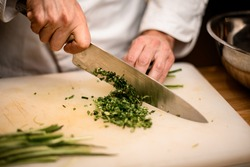 Close-up of hands of chef gently chopping green onion with sharp knife on cutting board