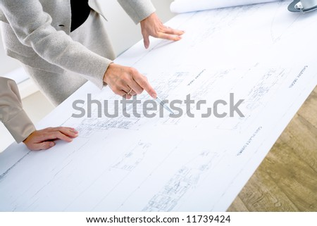 Close-up of hands of female architects working on blueprint.