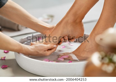 Close up of hands of masseur washing feet of woman in spa in grey bowl with water. Girl getting spa massage treatment in luxury beauty salon: foot reflexology and chiropody therapy.
