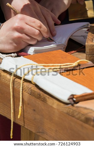 Close up of hands of scribe practicing traditional illumination writing calligraphy with feather quill and ink #726124903