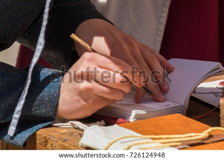 Close up of hands of scribe practicing traditional illumination writing calligraphy with feather quill and ink #726124948
