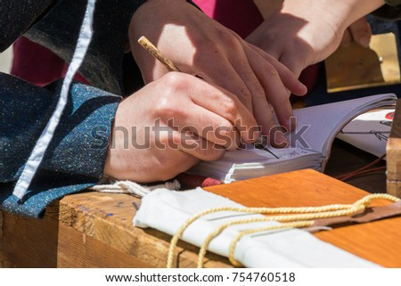 Close up of hands of scribe practicing traditional illumination writing calligraphy with feather quill and ink #754760518